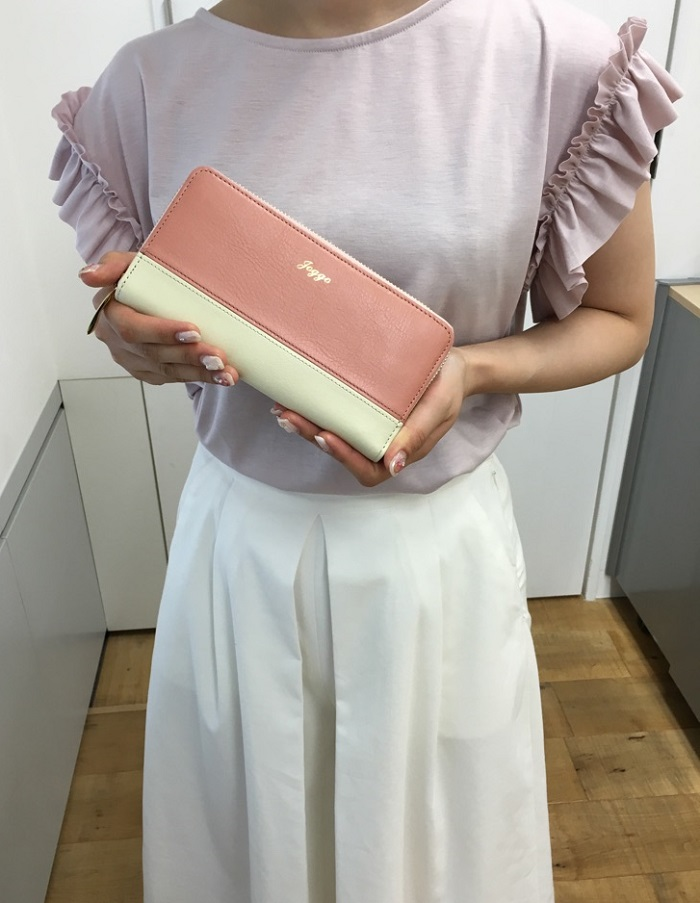 JOGGOのラウンドファスナー財布を持っているところ
