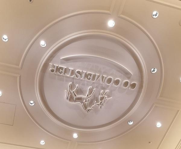 ココマイスター神戸旧居留地店(神戸市中央区 京町25番地 神戸旧居留地25番館 1F)の財布売り場の天井に刻まれたココマイスターのロゴ